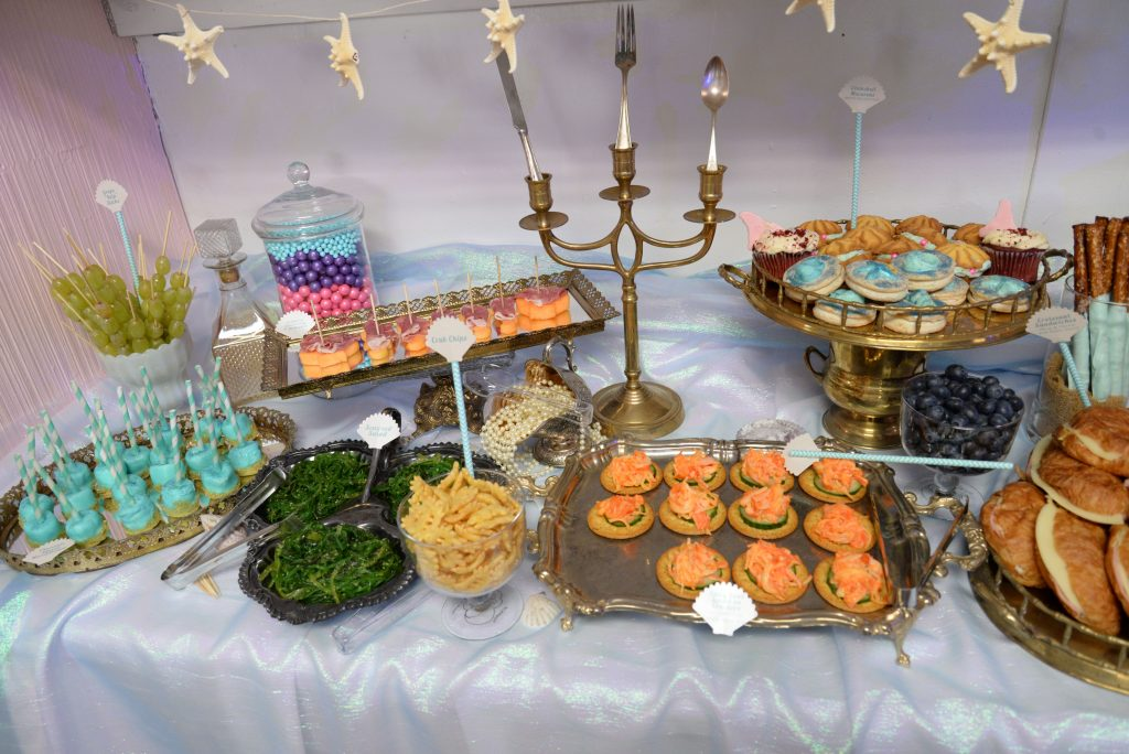 Mermaid launch party dessert and appetizer spread with vintage platters and decor