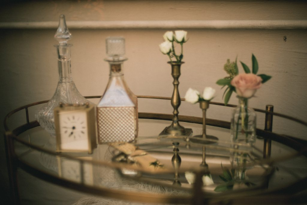 Vintage bar table with decanters, candle holders, and cigar bar. Vintage Wedding.